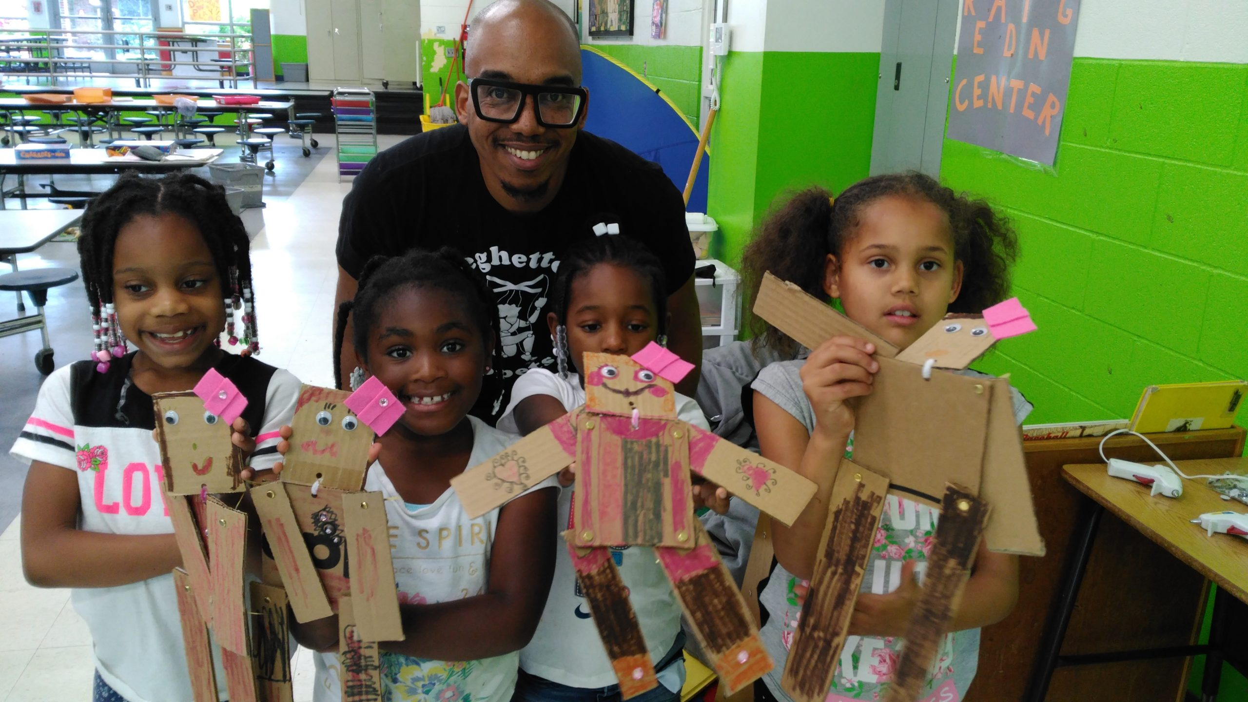 Four children show the camera their hand made puppets. The teaching artist stands behind them