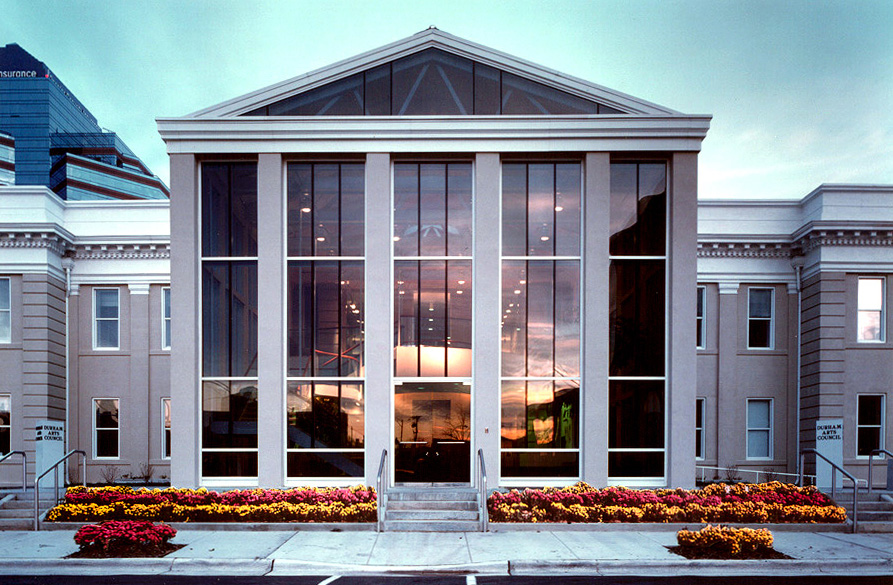 View of the front of the DAC building at dusk from across Morris Street, the sunset is reflected in the glass of the building.