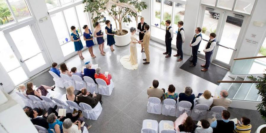 A wedding ceremony takes place in the pavilion with guests seated watching. The view is from above
