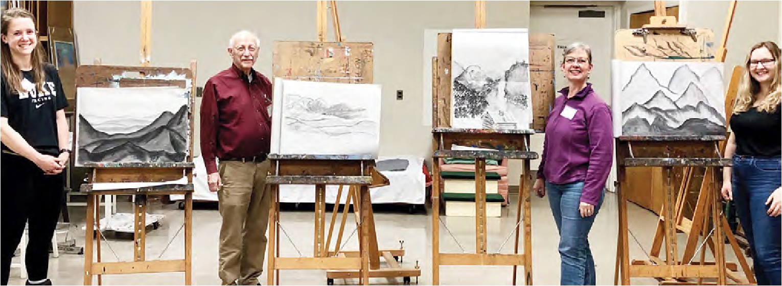 Four students stand next to their pencil drawings of a mountain scene smiling at the camera