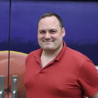 A man in a red shirt stands in front of a purple wall