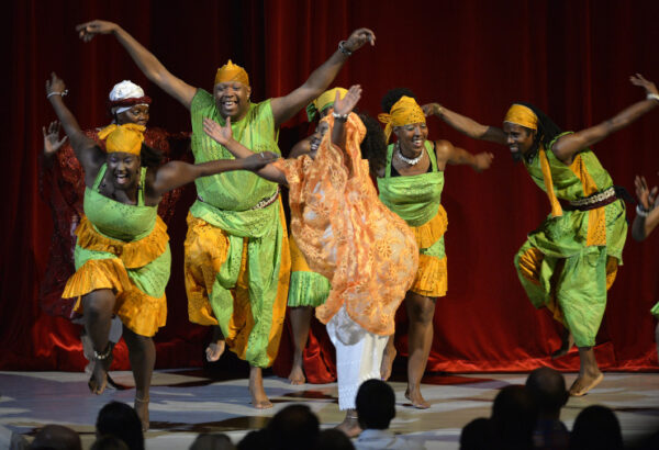 A group of dancers perform African dance in traditional costumes and bare feet on stage with a red curtain behind
