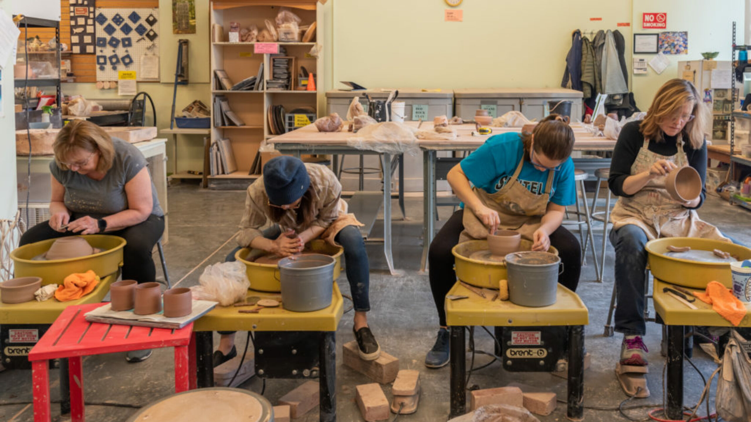 Four female students work at pottery wheels in a row