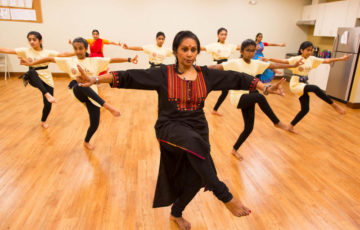 Woman leads a group of children in Indian Dance