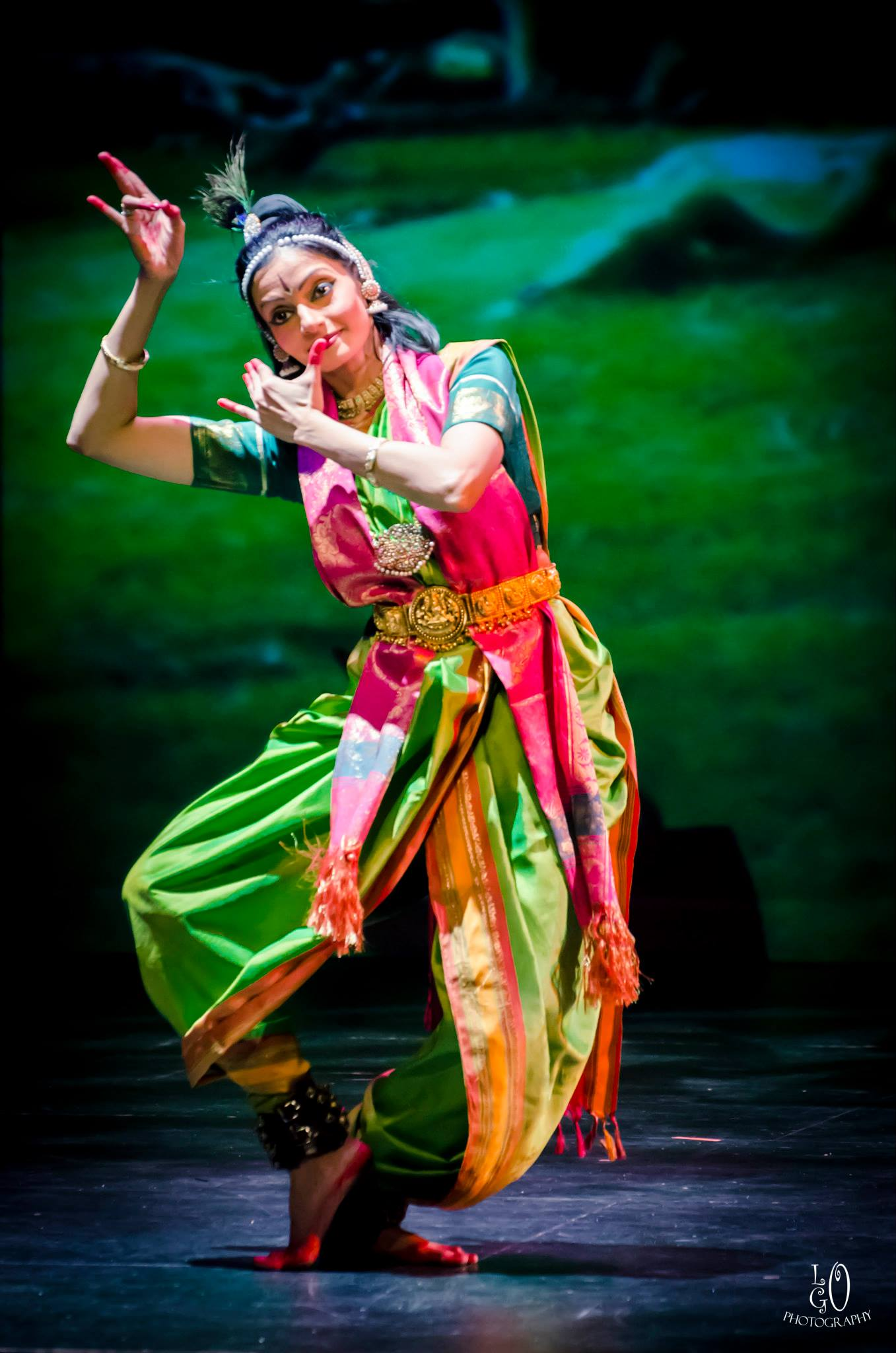 Indian dancer in colorful traditional clothing performs on stage with a green background