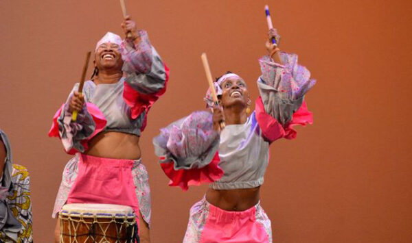 Two women in bright costumes hold drum sticks in the air during a performance