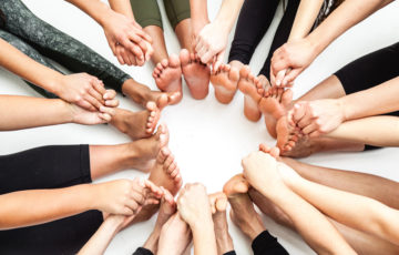 Birds-eye view of a circle of bare feet and hands. The hands are held with each other and the feet are all touching to form a ring