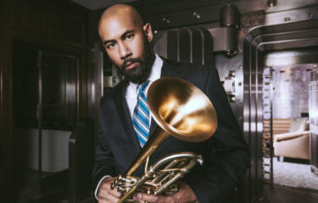 Man wearing a suit poses with a trumpet