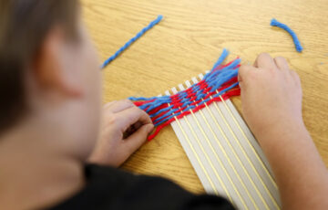 Looking over the shoulder of a child who is weaving pieces of wool onto a simple craft loom