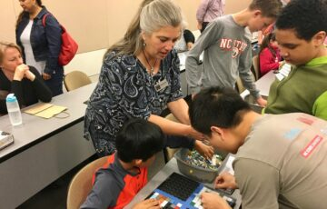 Woman helps children play with mosaic tiles