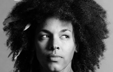 Black and white headshot of woman with feathers poking out of her natural hair