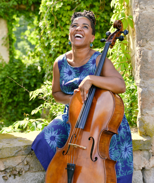 Woman laughs while holding cello outside in sunshine