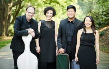 Four people dressed in formal black outfits pose with their string instrument cases
