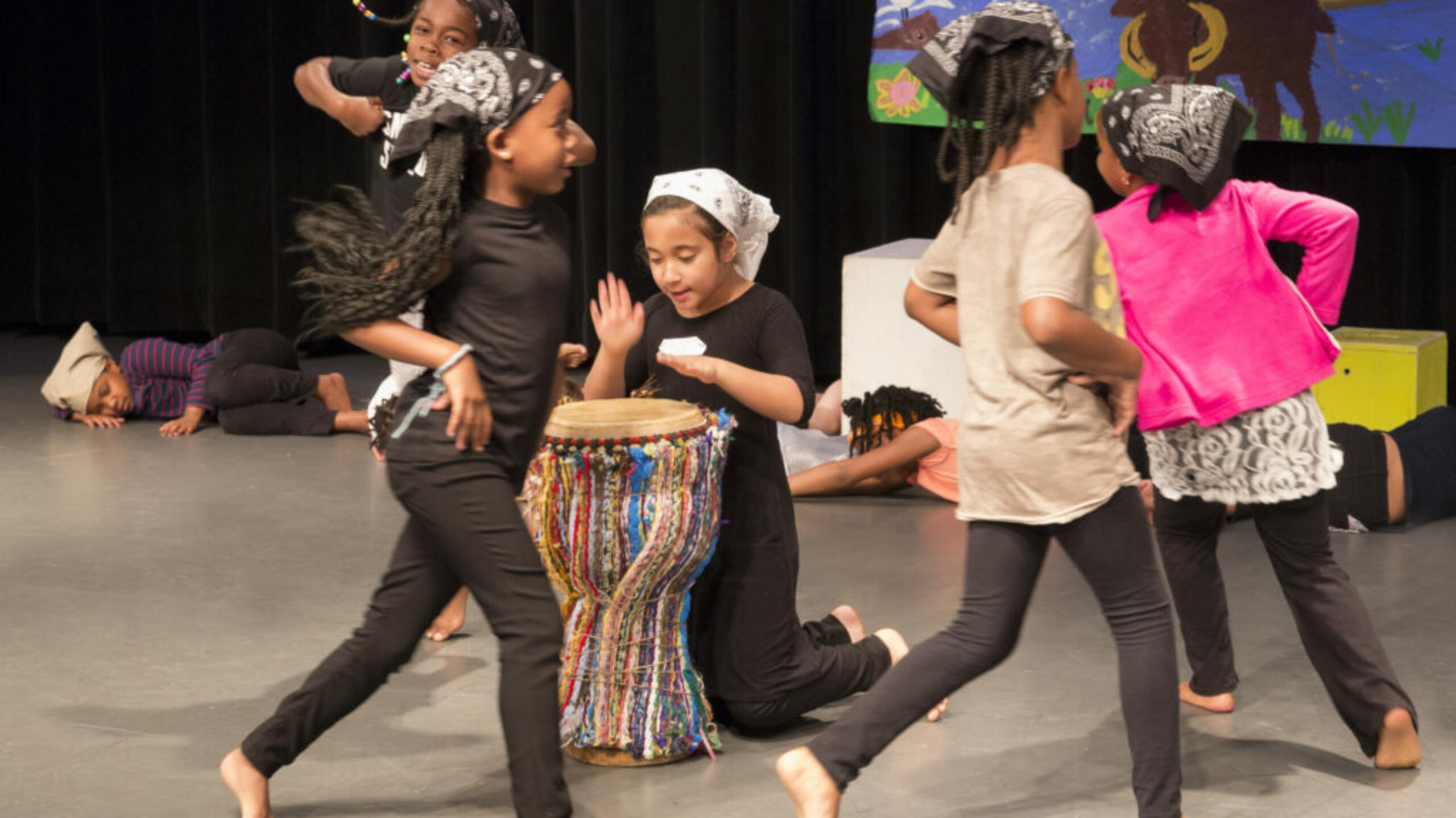 One child hits a drum on stage as four other children dance around her. They all swear head scarves