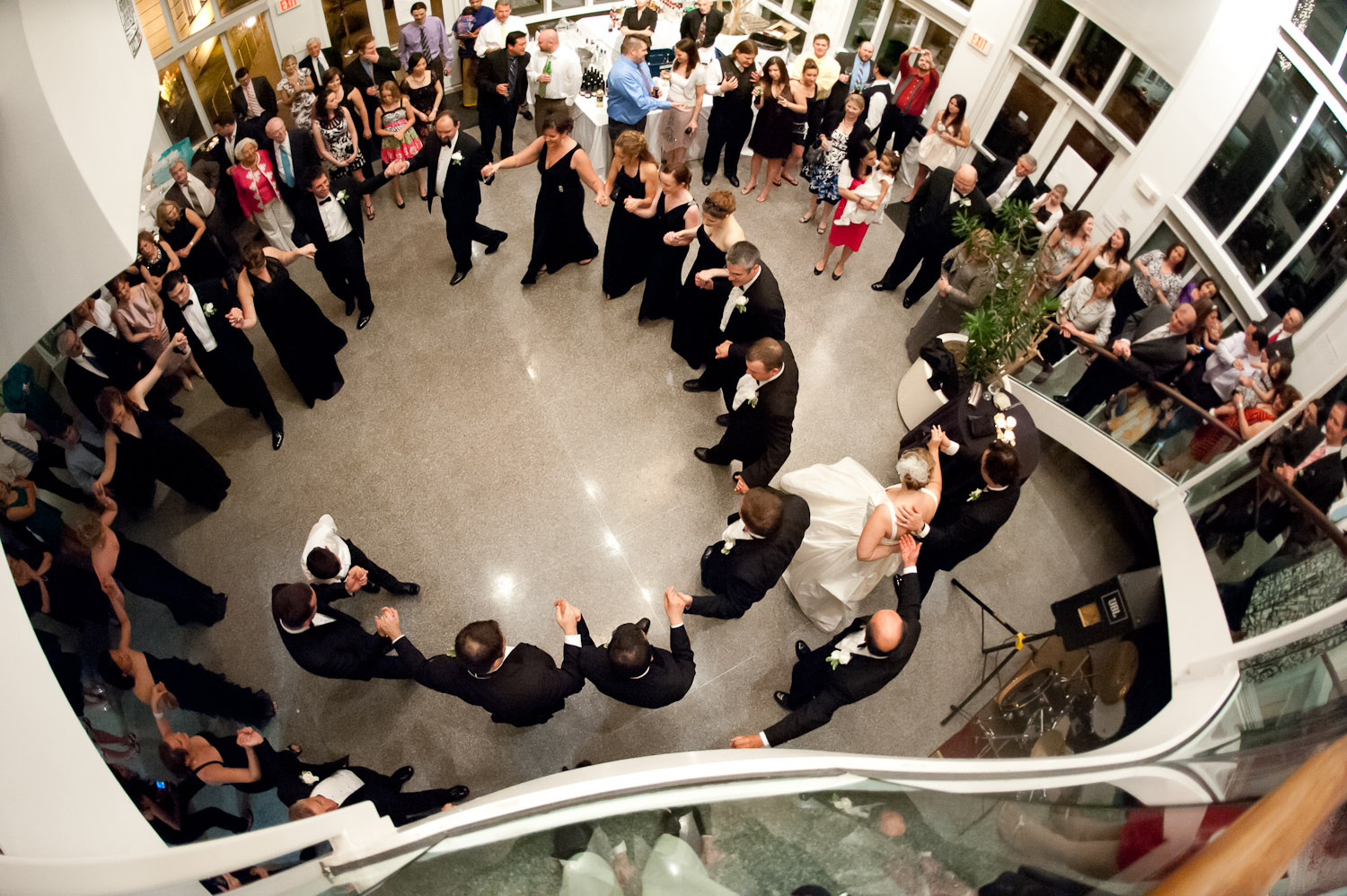 Birdseye view of the pavilion with a large group of wedding guests dancing in a circle formation