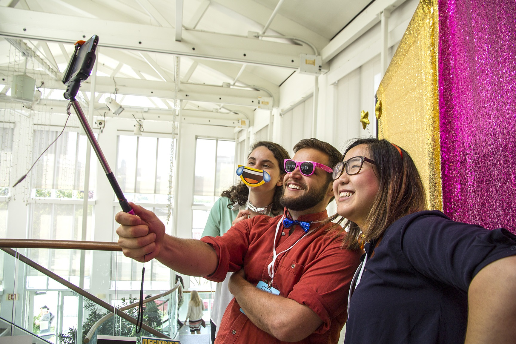 Picture of 3 people taking a selfie using fun props in front of a sparkly background