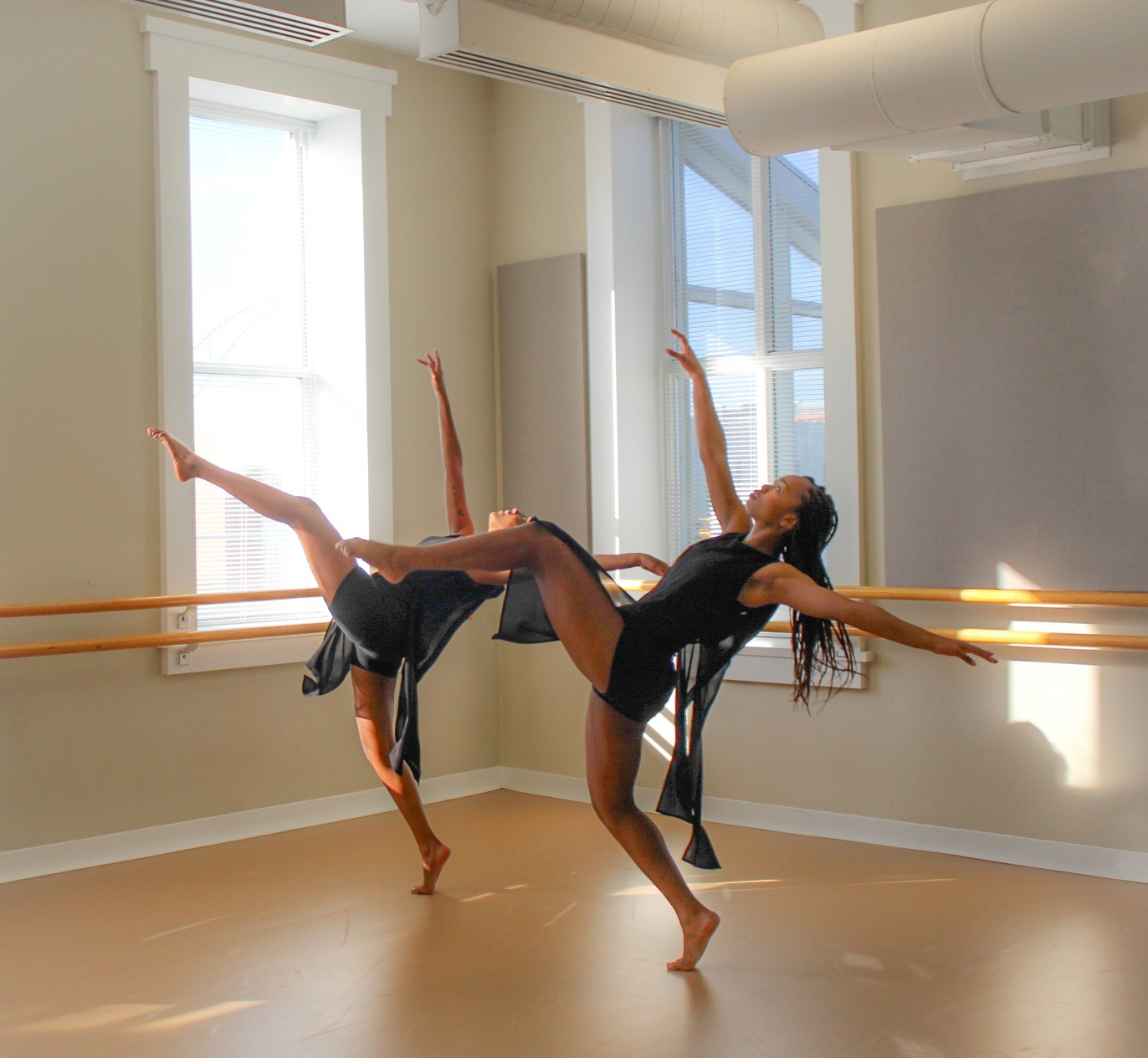 Two women dressed in black shorts and flowing tops dance in the corner of a clean dance studio in front of windows
