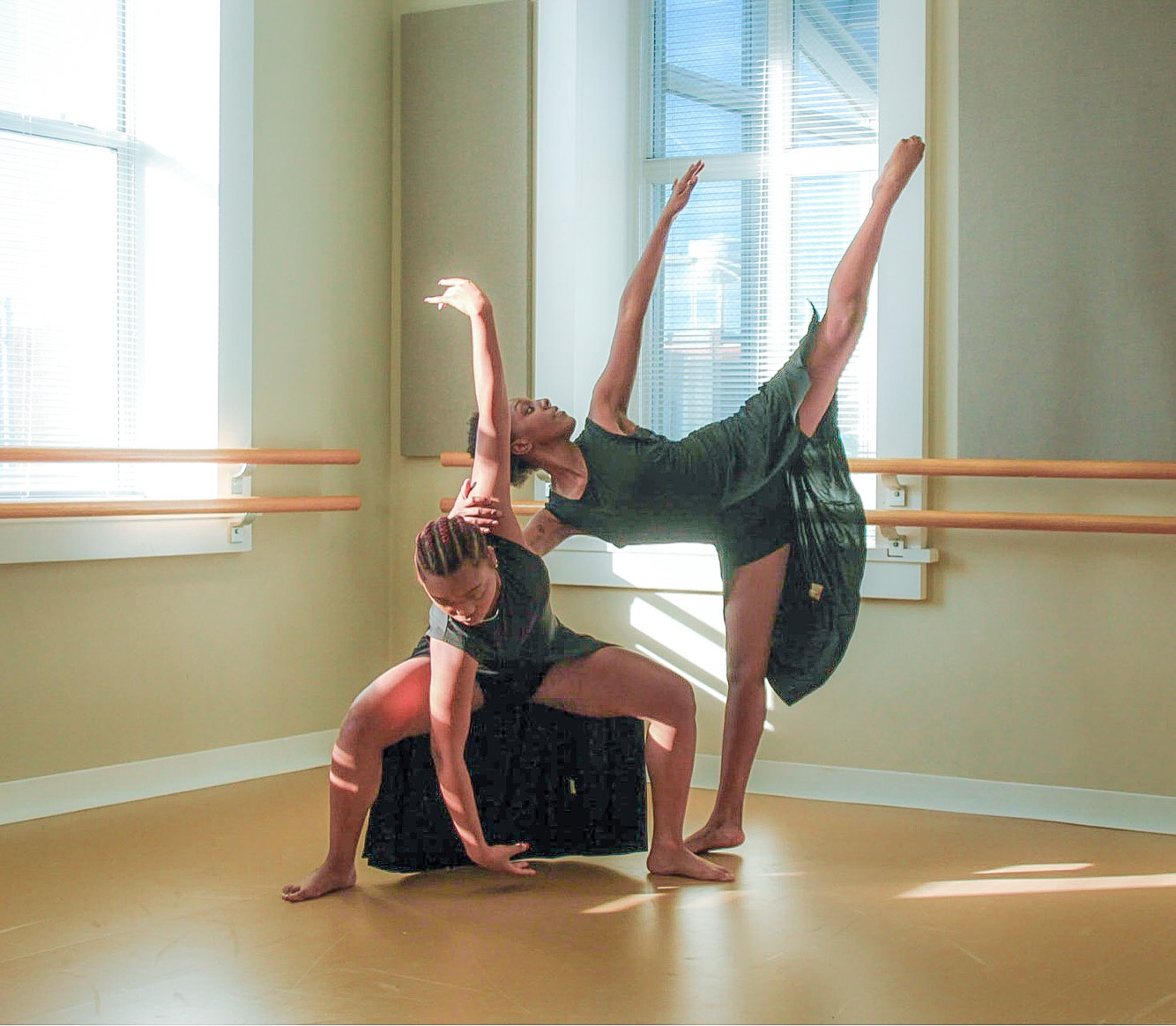 Two women dressed in green shorts and flowing tops dance in the corner of a clean dance studio in front of windows