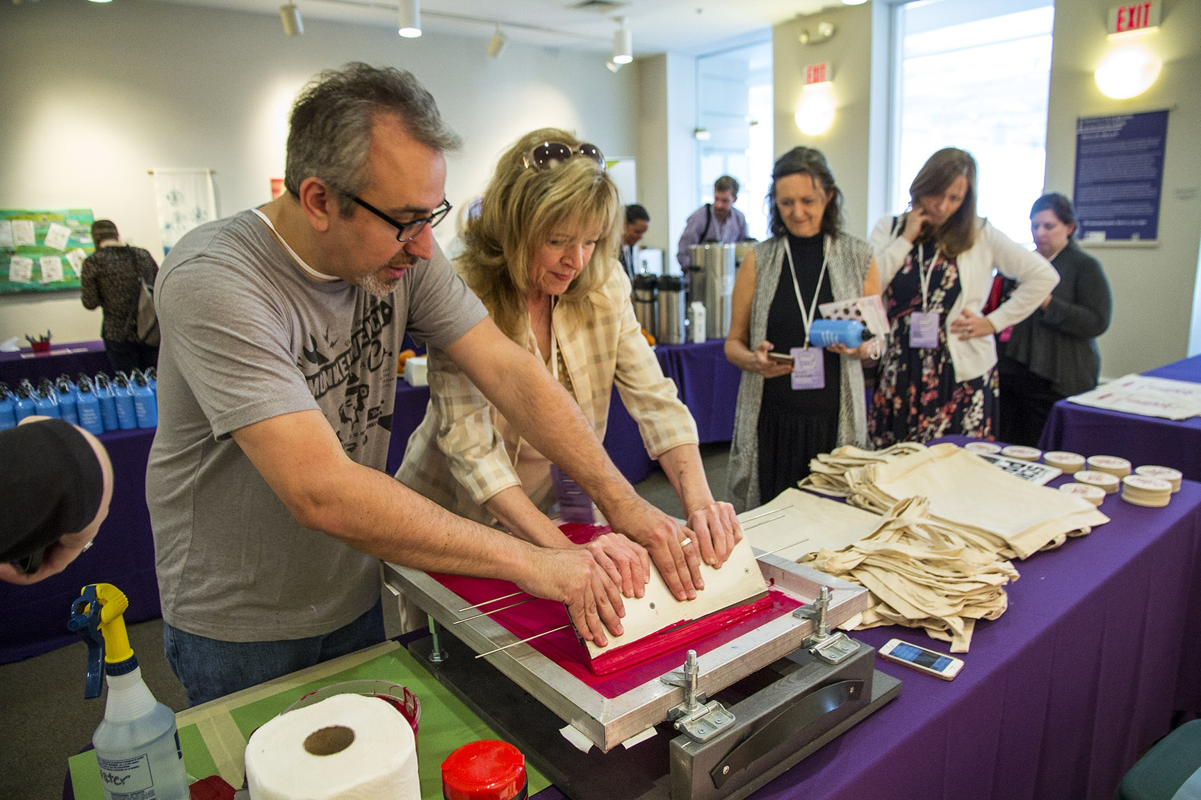 Man helps woman create a screen print on a tote bag during a break at a conference