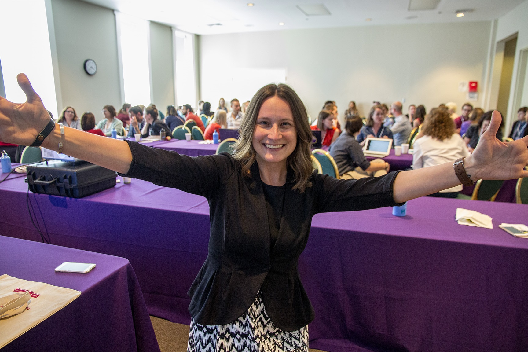 A woman leading a meeting smiles and extends her arms to the camera in front of the room full of meeting participants