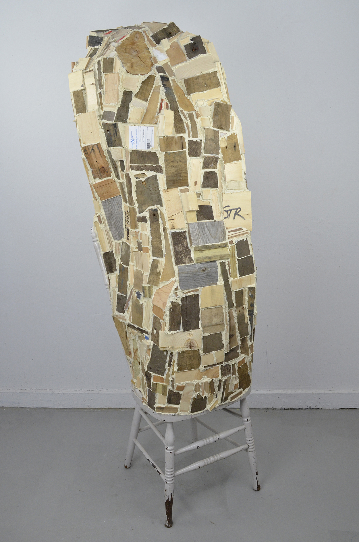 An art installation sculpture of the bottom legs of a stool with an undulating tower made of small, uneven rectangles of wood grouted together