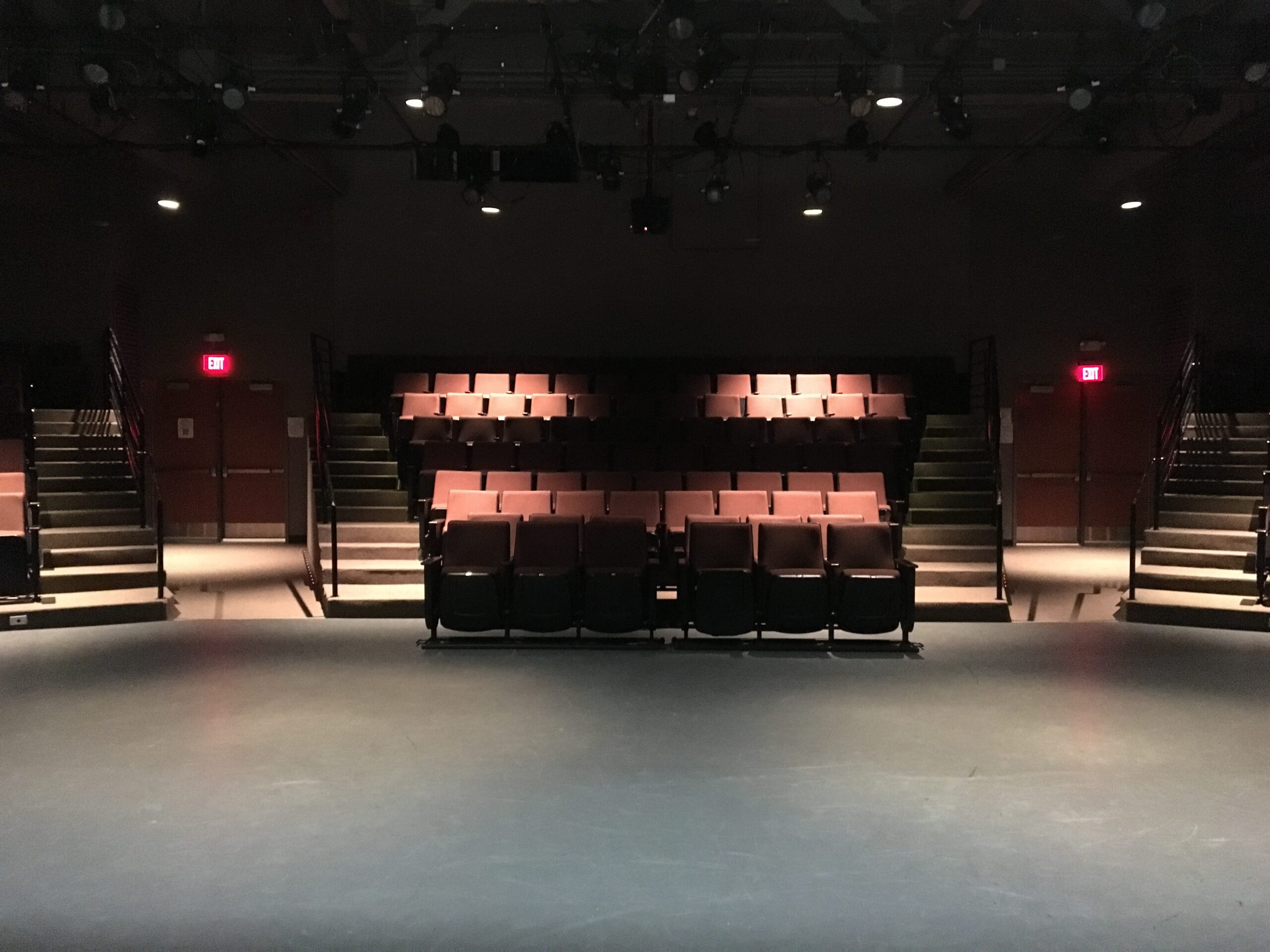 Image taken from the stage of an empty theatre looking out at the seating
