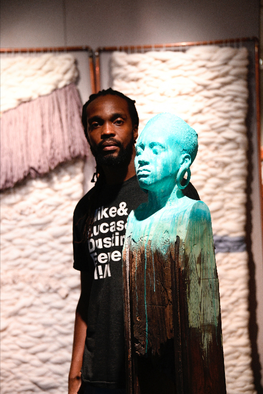 A male artist stands behind a sculpture of a female bust with bright paint dripping down it
