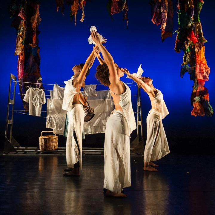3 women dressed in all cream with their arms raised performing a contemporary dance in front of a dark blue background with a washing line in the background and red and multicolored rags hanging from above