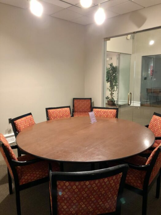 Chairs are positioned around a circular conference table in an empty room