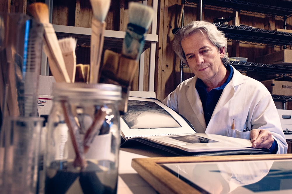 A man wearing a lab coat looks through a book of photographs. There is a jar of paint brushes in the foreground