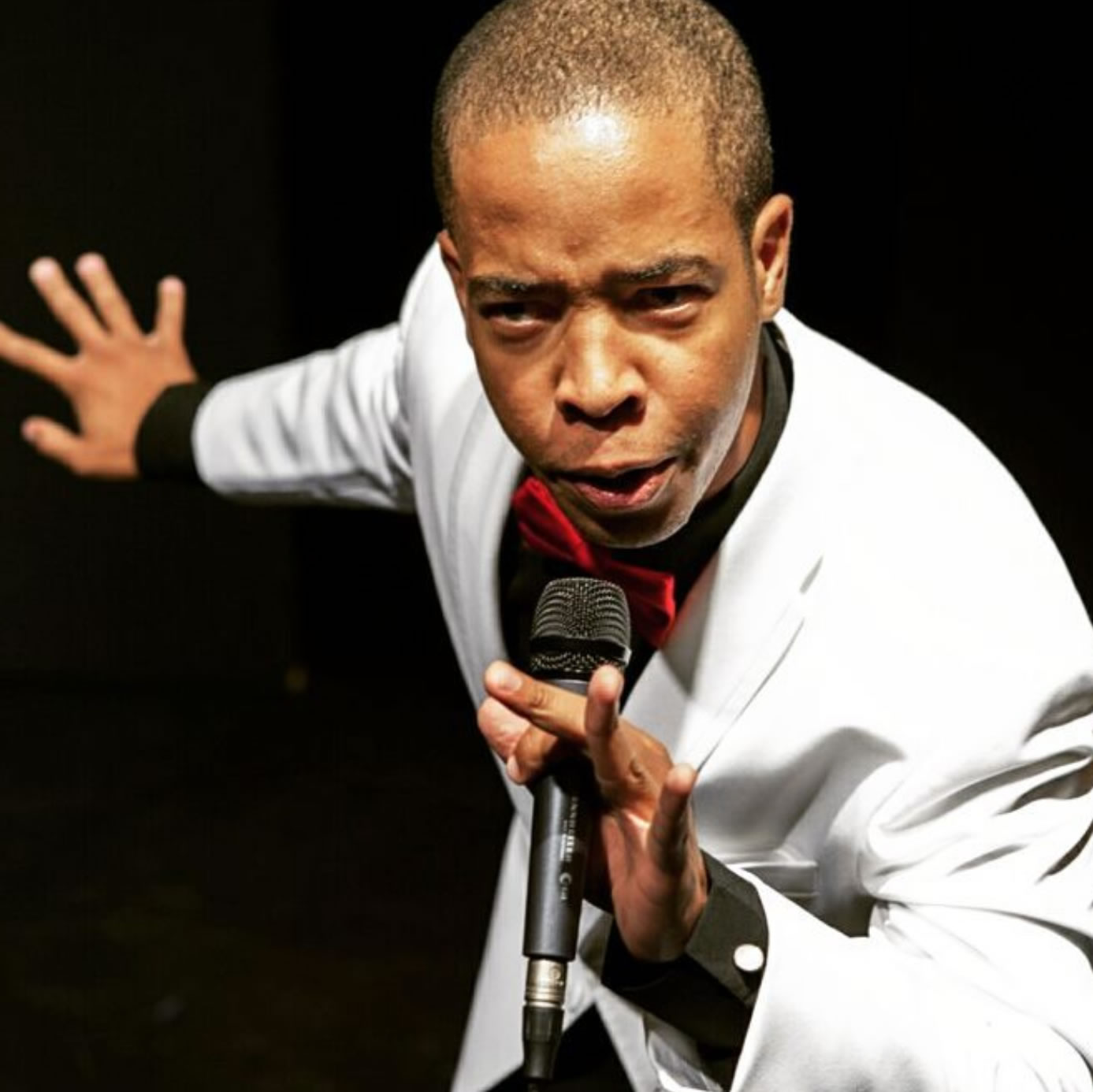 A man on stage wearing a white suit holds a microphone and leans forward toward the camera