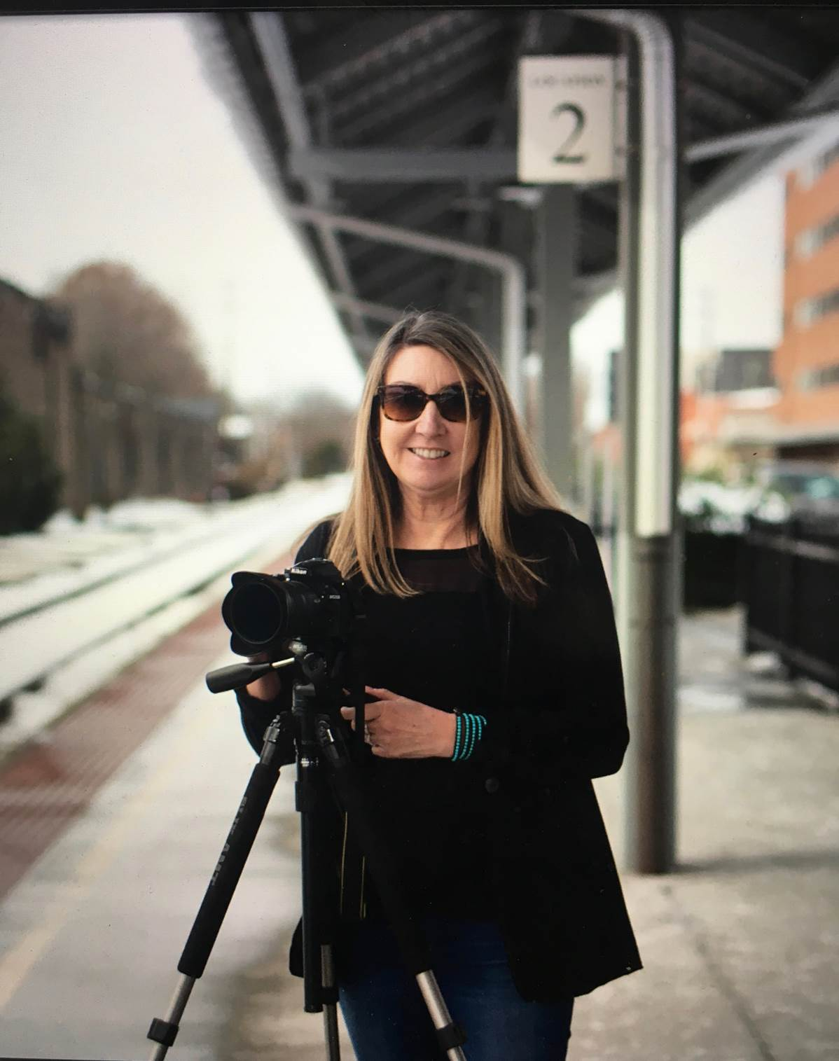 A woman stands on a train platform with a camera on a tripod smiling