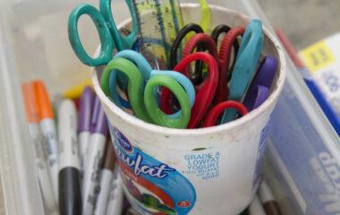An old yogurt pot filled with children's art supplies