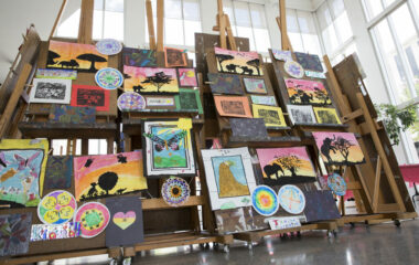 Easels covered in children's art work on display