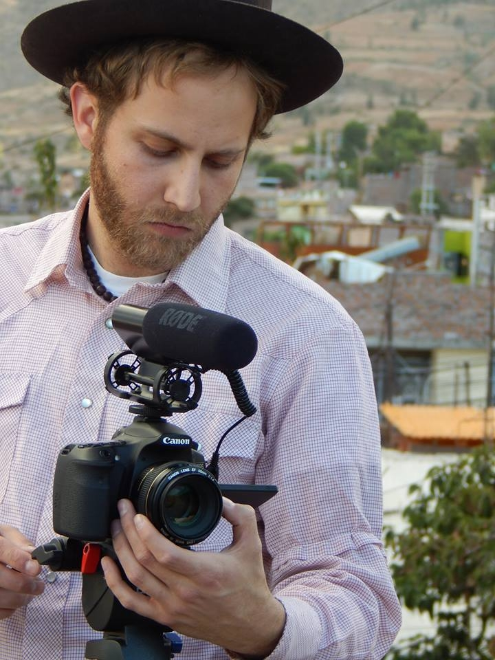 A man wearing a hat adjusts a digital camera on a tripod