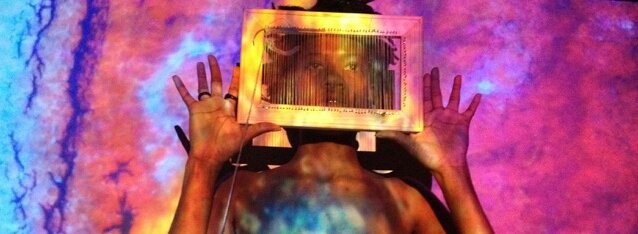 Image of a Black woman holding up a frame in front of her face. A projection of a mixture of very bright colors is projected onto her