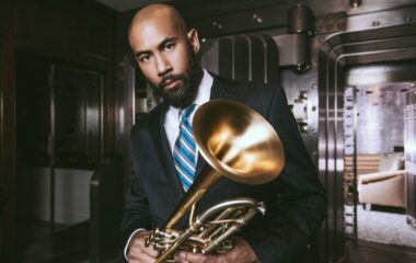 A musician in a suit and tie looks into the camera and holds a trumpet