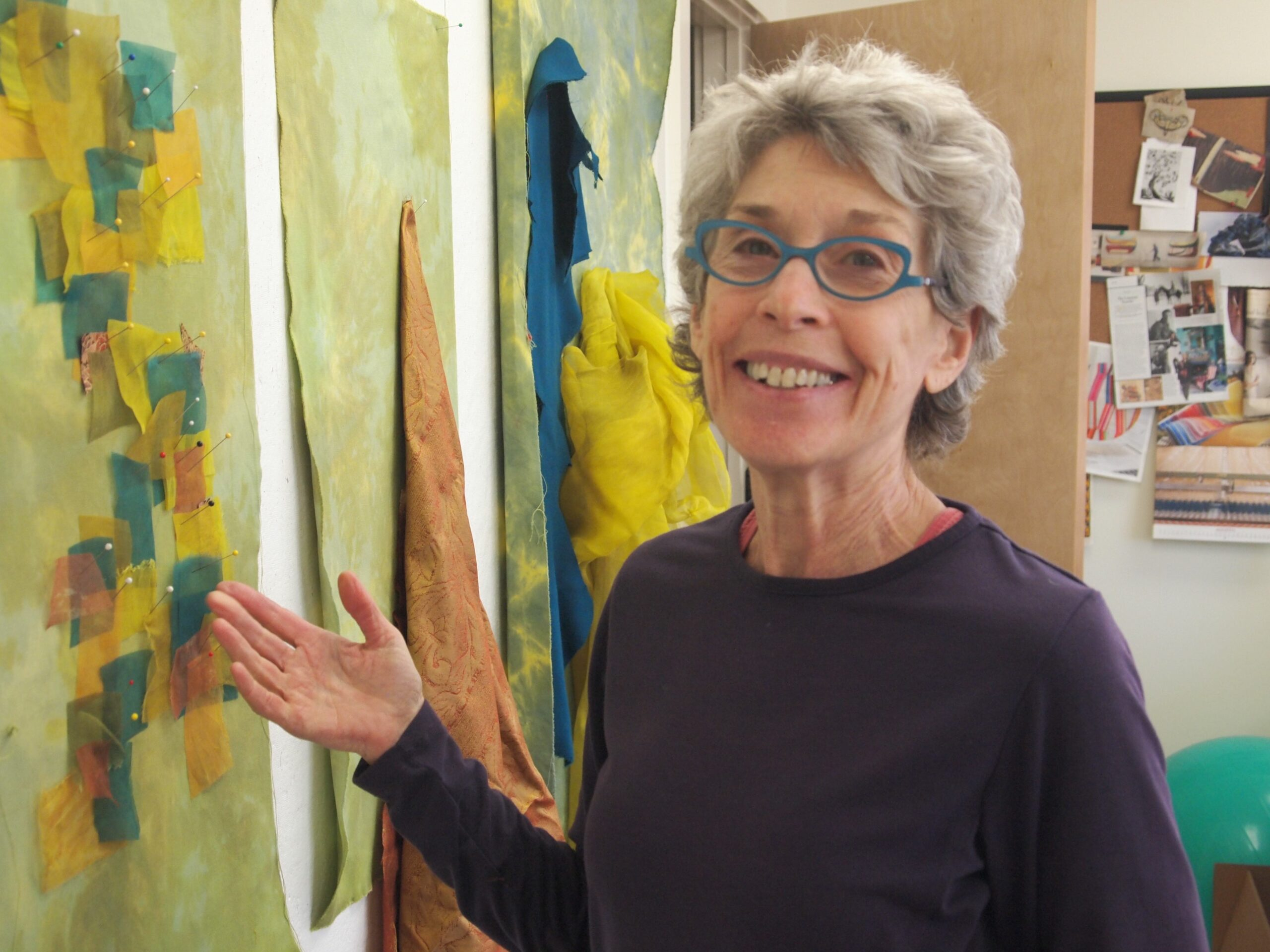 A woman gestures towards a piece of fiber art hanging on the wall beside her while smiling at the camera