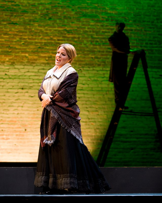 A woman dressed in period clothing sings on a stage. There is a man on a ladder in the shadow behind her