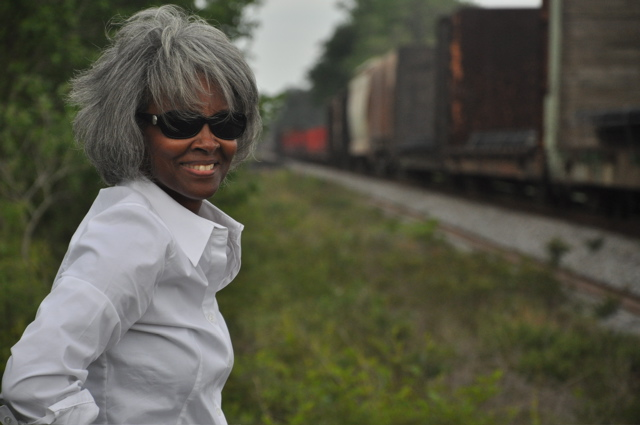 A woman in sunglasses smiles at the camera, a train passes her on tracks in the background