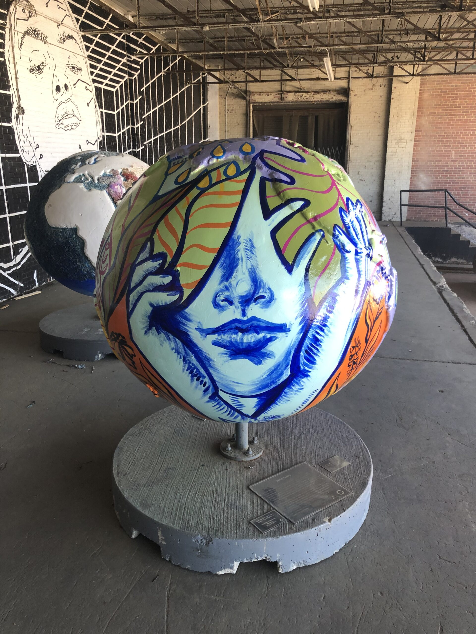 Globe painted with a monotone face cradled in two hands surrounded by bright tropical leaves