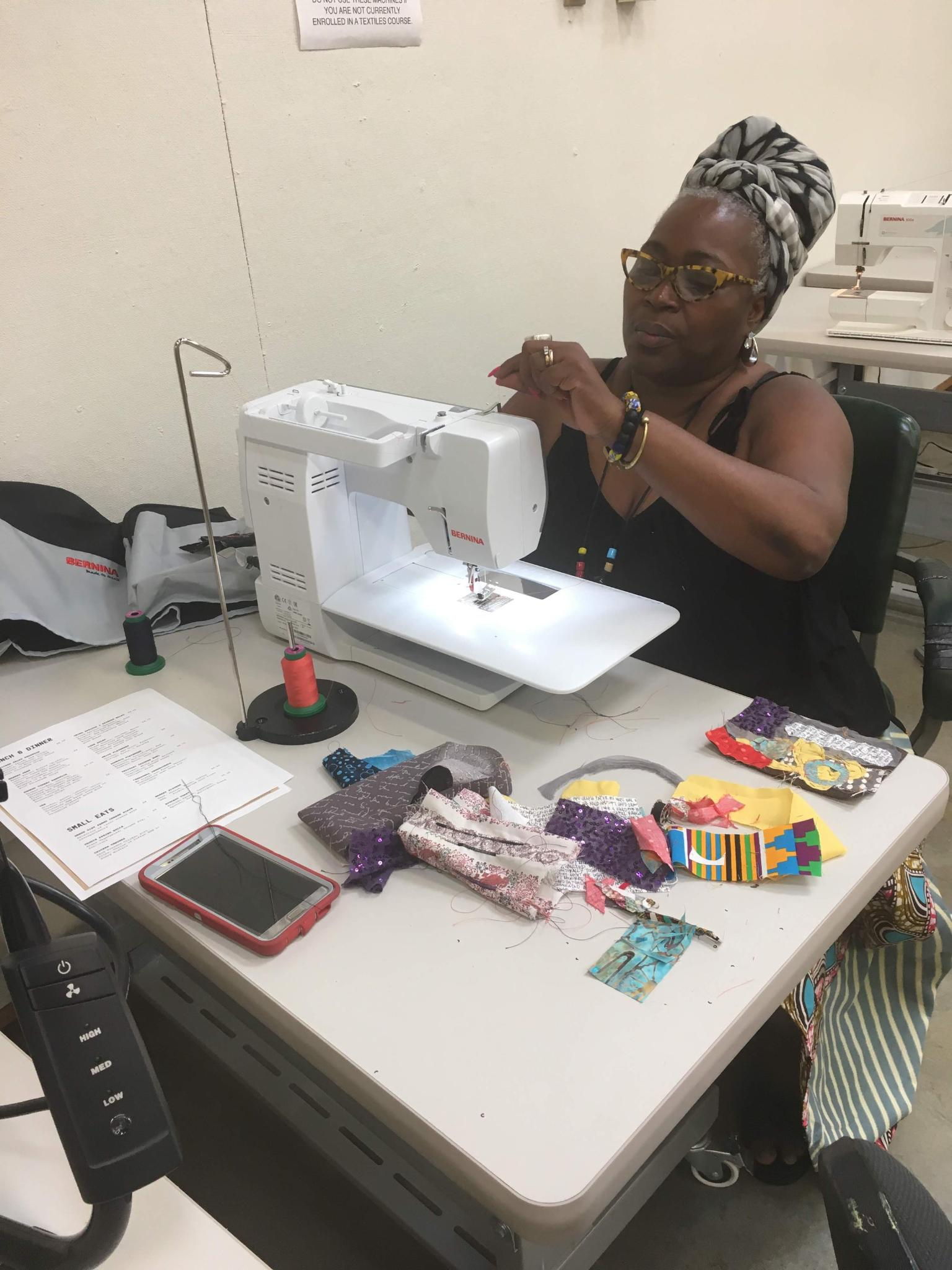 A woman sits behind a sewing machine making adjustments