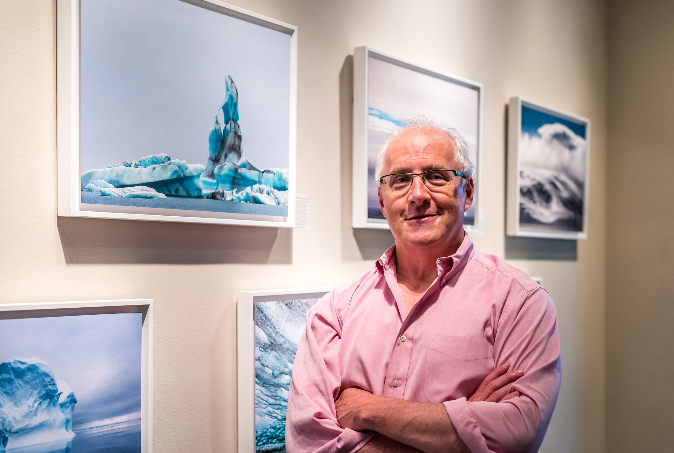 A man stands in front of a gallery wall with images of icebergs with arms folded in front of him