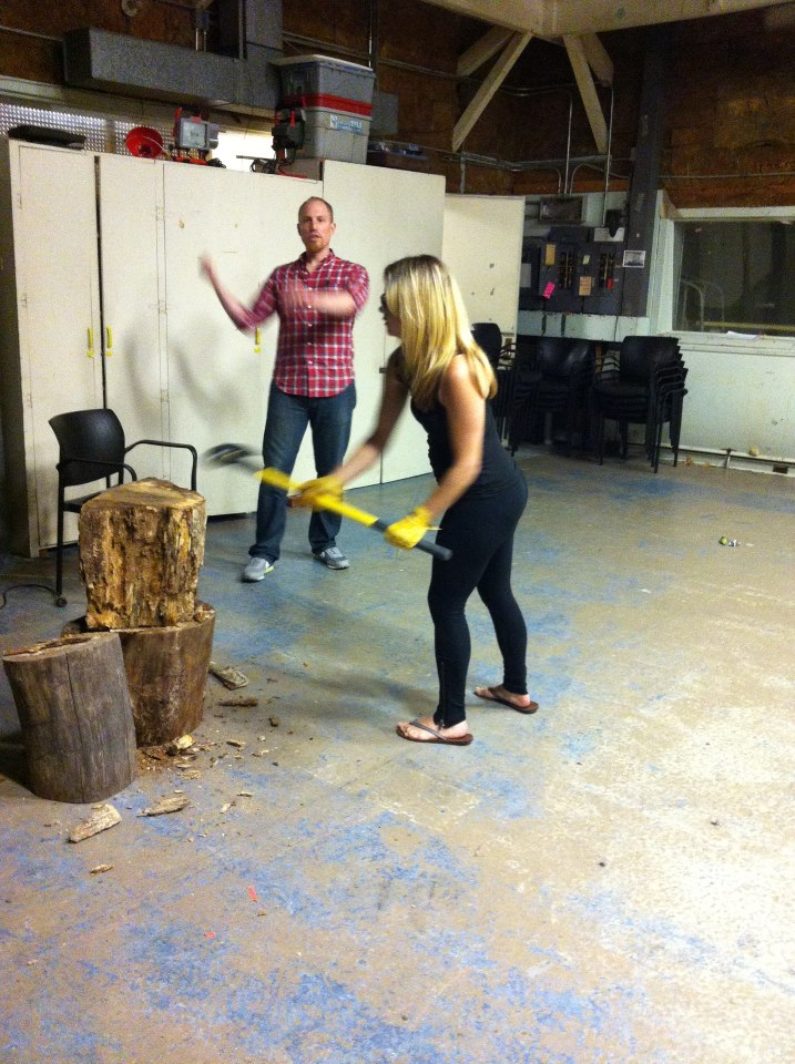 A woman swings an axe toward a stump of wood in a garage. A man is in the background appearing to demonstrate how she should do it