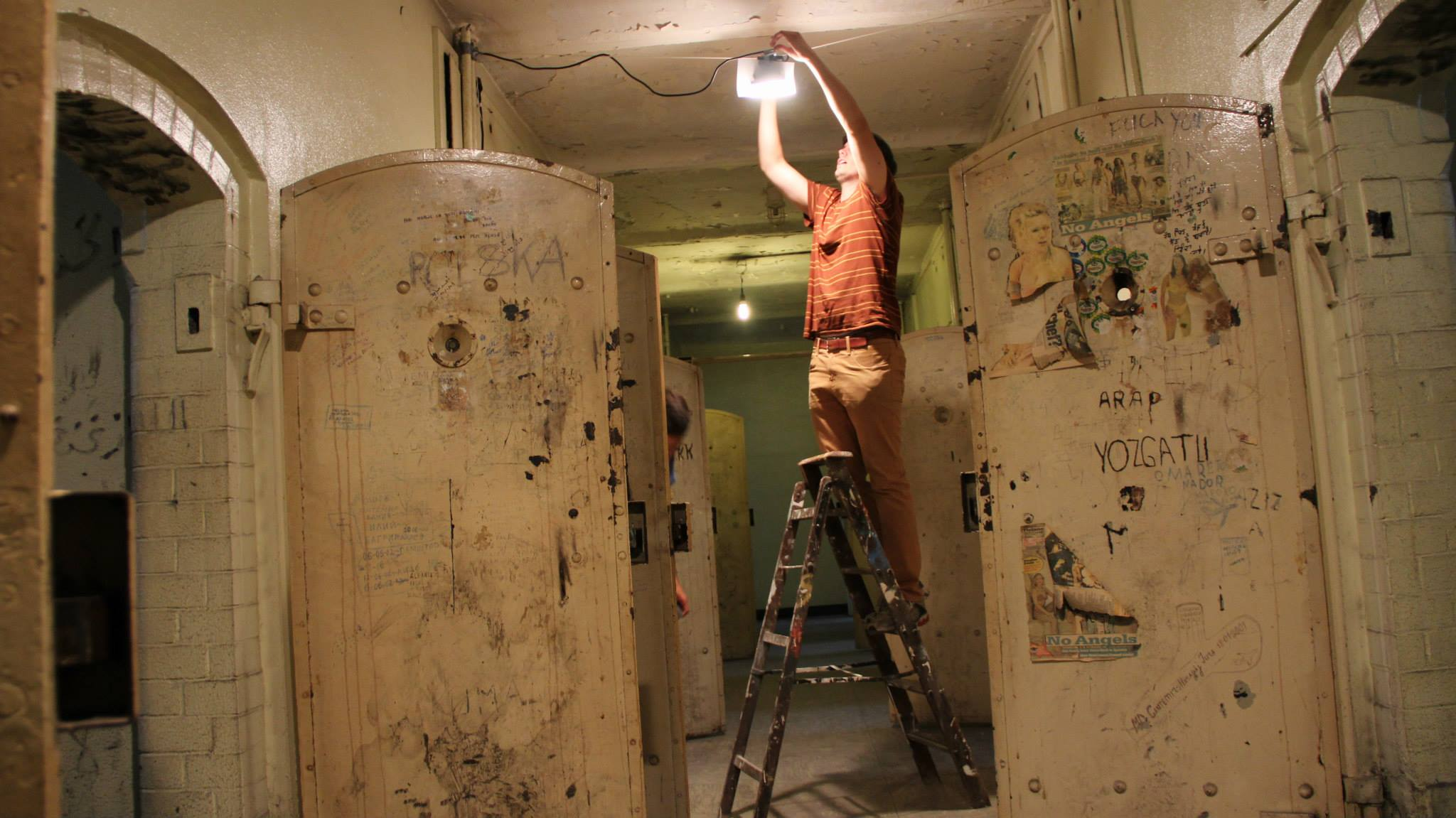 A man stands on a ladder and adjusts a light hanging overhead. He appears to be inside an abandoned building