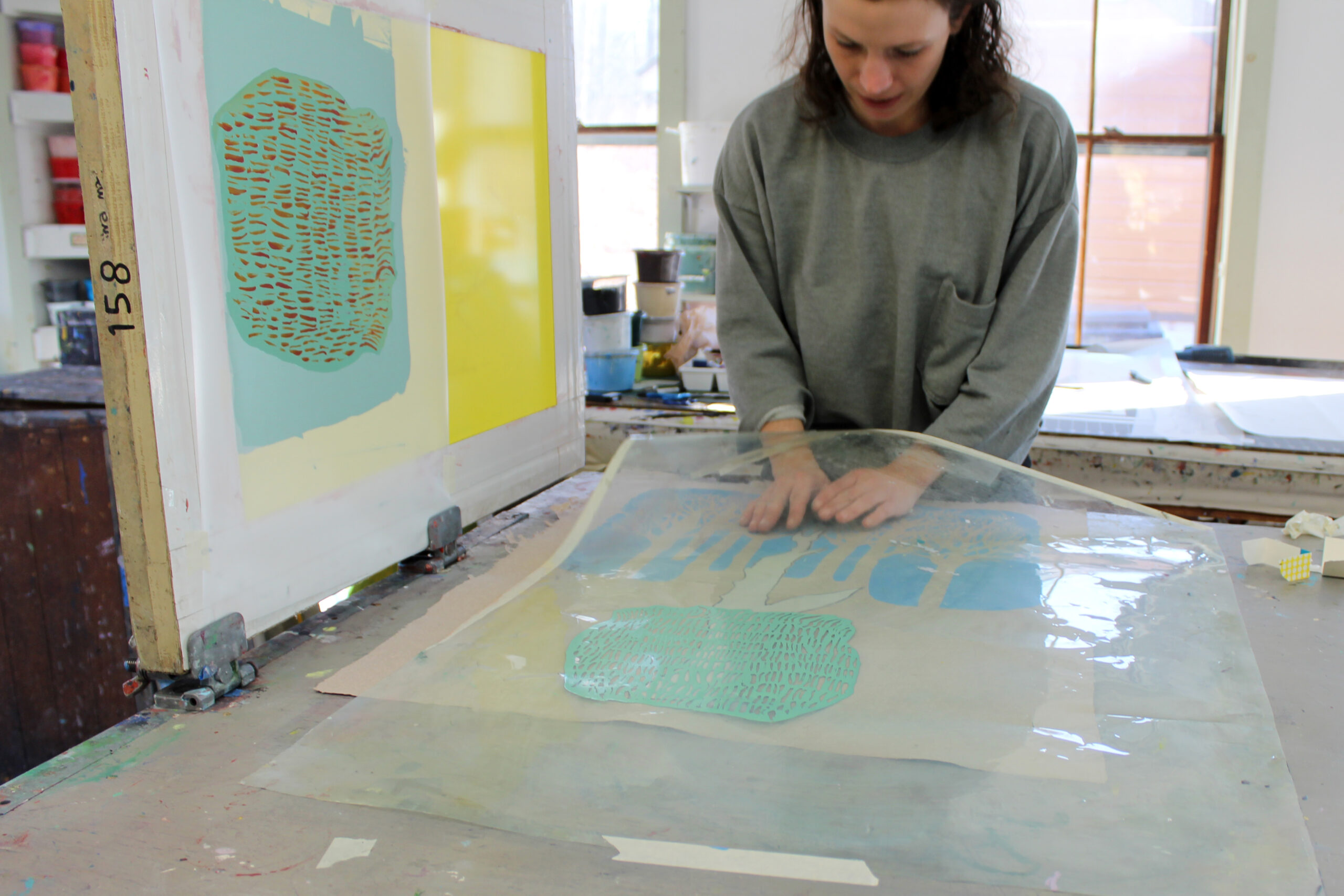 A woman leans over the artwork she is making. Her hands are under a clear plastic sheet