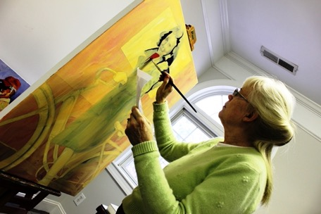 A woman works on a painting on an easel in front of her.