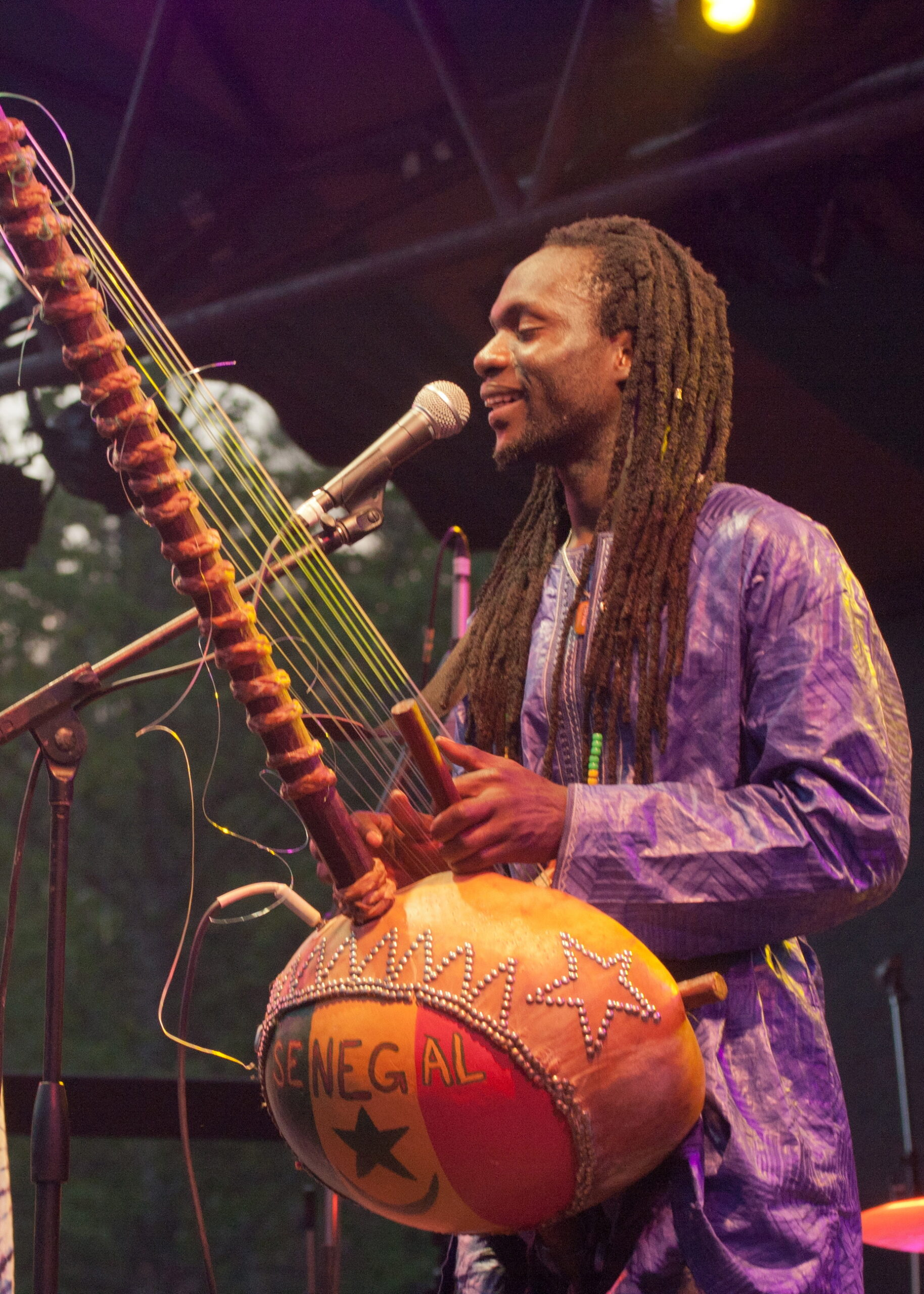 "A man plays a kora and sings into a microphone on a stage. The Koro has ""Senegal"" written on it"