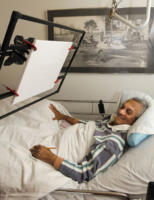 An older man laying in a hospital style bed holds a pencil and smiles at the camera. There is a rig above the bed that holds a canvas at an angle he could draw on from the bed