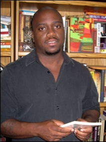 Headshot of a man holding a book standing in front of a full book shelf